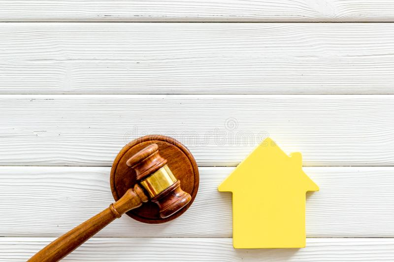 Inheritance of the house concept with figure and gavel on white wooden background top view space for text. Inheritance of the house concept with house figure and royalty free stock images