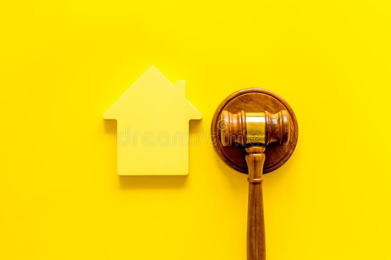 Inheritance of the house concept with figure and gavel on yellow background top view. Inheritance of the house concept with house figure and inscribed gavel on royalty free stock photos