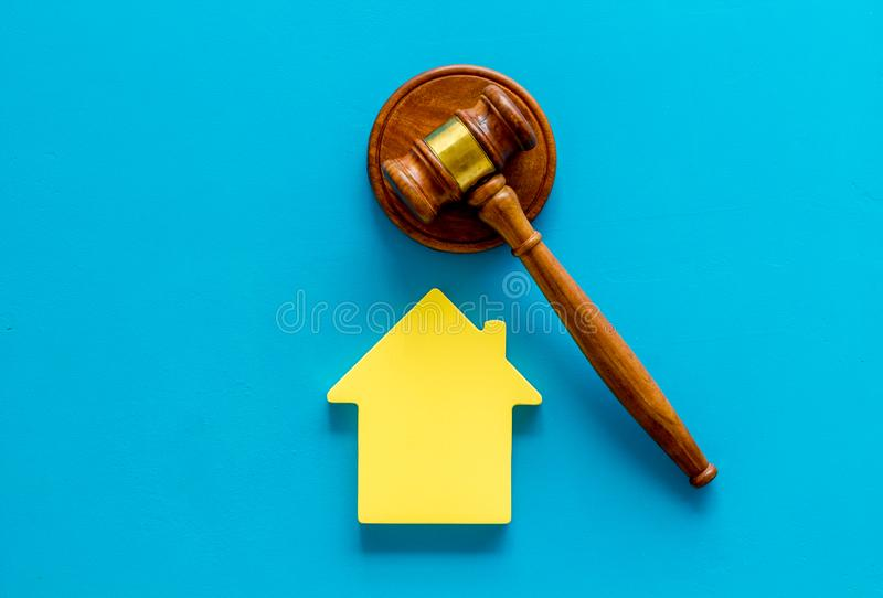 Inheritance of the house concept with figure and gavel on blue background top view. Inheritance of the house concept with house figure and inscribed gavel on stock images