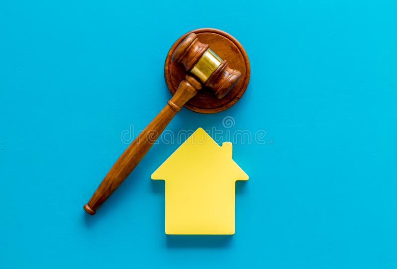 Inheritance of the house concept with figure and gavel on blue background top view. Inheritance of the house concept with house figure and inscribed gavel on royalty free stock photography