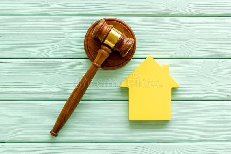 Inheritance of the house concept with figure and gavel on mint green wooden background top view. Inheritance of the house concept with house figure and inscribed stock photo