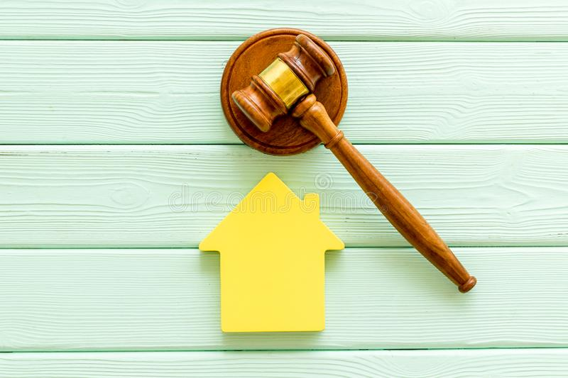 Inheritance of the house concept with figure and gavel on mint green wooden background top view. Inheritance of the house concept with house figure and inscribed royalty free stock photo