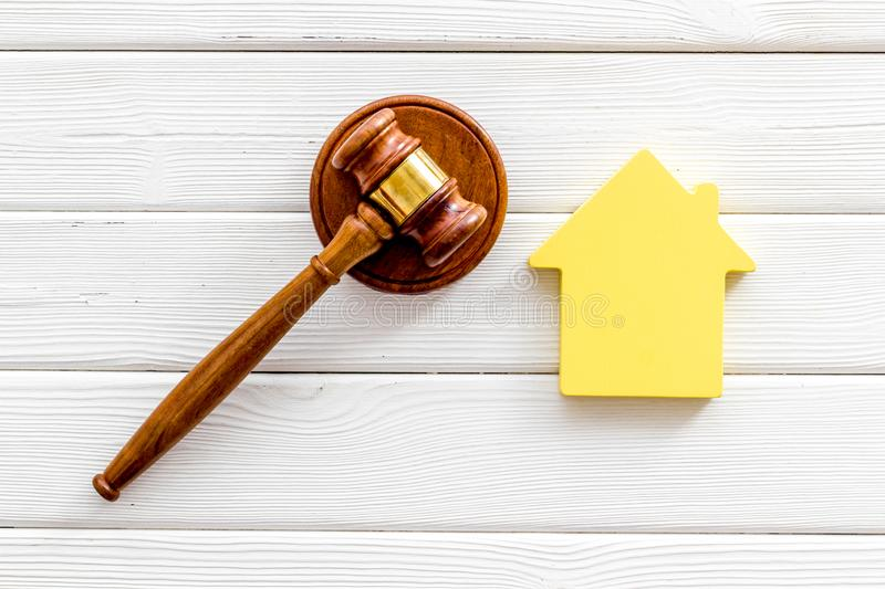 Inheritance of the house concept with figure and gavel on white wooden background top view. Inheritance of the house concept with house figure and inscribed stock image