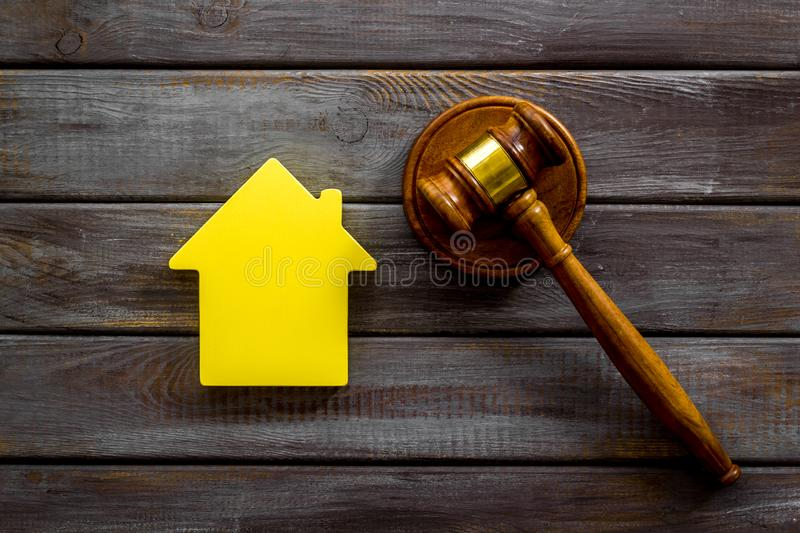 Inheritance of the house concept with figure and gavel on wooden background top view. Inheritance of the house concept with house figure and inscribed gavel on stock images