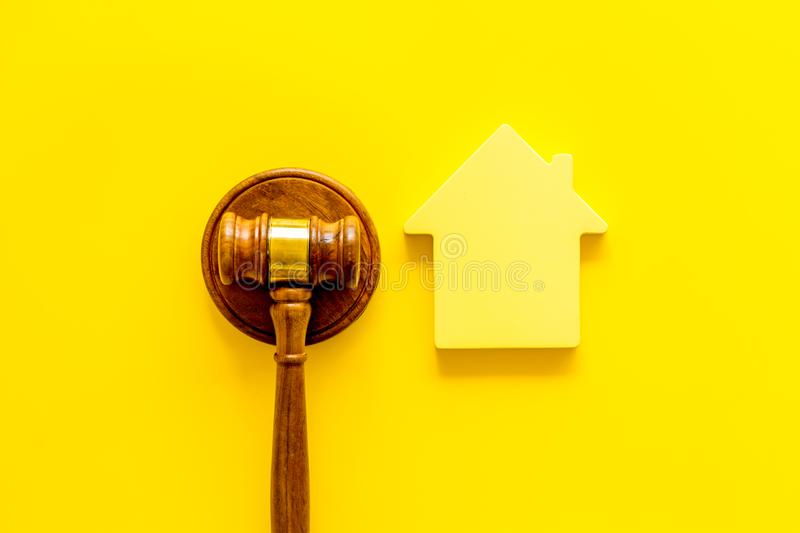 Inheritance of the house concept with figure and gavel on yellow background top view. Inheritance of the house concept with house figure and inscribed gavel on stock images