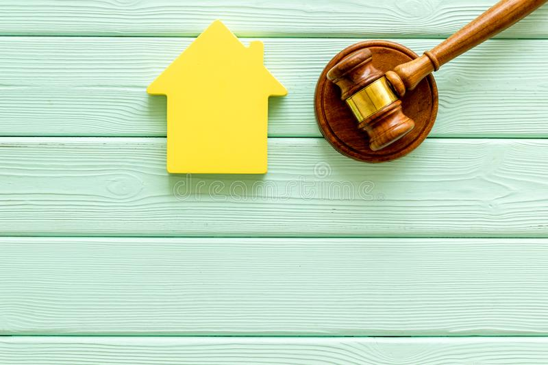 Inheritance of the house concept with figure and gavel on mint green wooden background top view space for text. Inheritance of the house concept with house stock photography