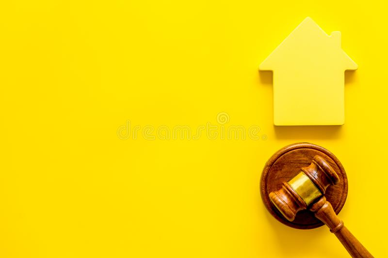 Inheritance of the house concept with figure and gavel on yellow background top view space for text. Inheritance of the house concept with house figure and royalty free stock images