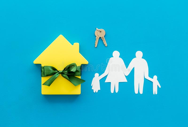 Inheritance house with family figure, keys on blue background top view.  royalty free stock images