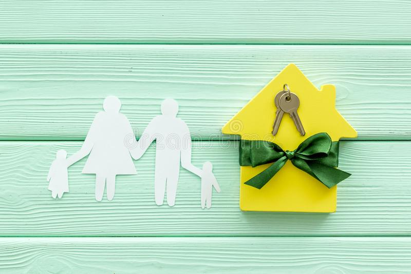 Inheritance house with family figure, keys on mint green wooden background top view.  stock photos