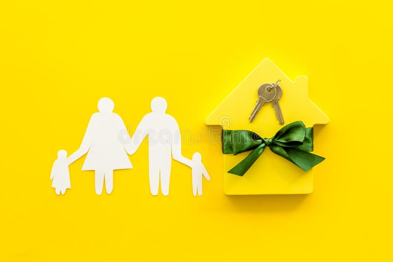Inheritance house with family figure, keys on yellow background top view.  stock photos