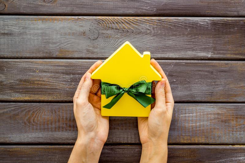 Inheritance house with figure in hands on wooden background top view.  stock image