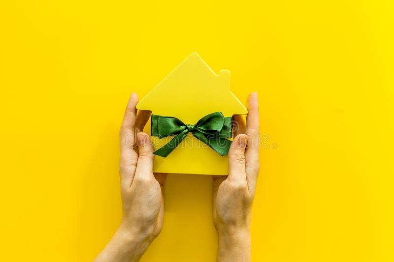 Inheritance house with figure in hands on yellow background top view.  royalty free stock images