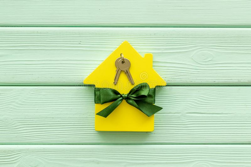 Inheritance house with figure and keys on mint green wooden background top view.  royalty free stock photos