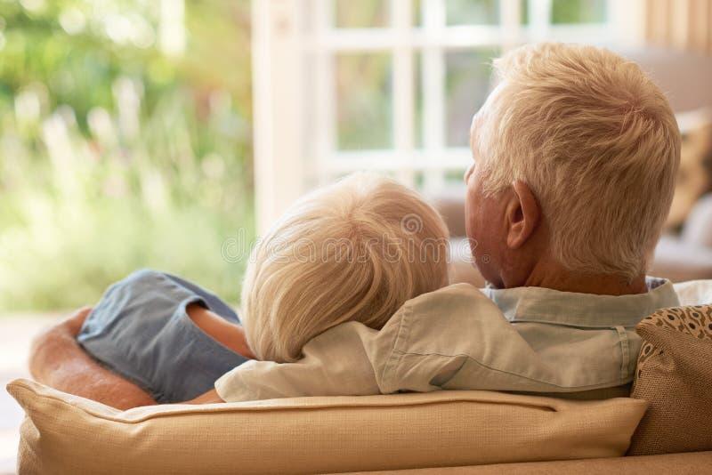 Inhouds het hogere paar ontspannen samen op hun bank thuis stock afbeelding