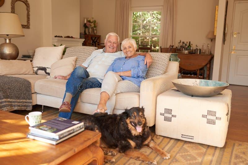 Inhouds het hogere paar ontspannen thuis met hun hond royalty-vrije stock fotografie