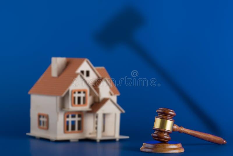 Inhysa auktionbegreppet - auktionsklubban och inhysa på blå bakgrund royaltyfri fotografi