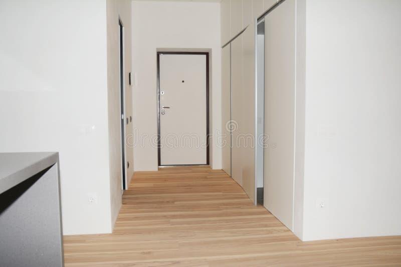 Inhysa ingångsdörren och entracekorridorinre med ädelträfloo royaltyfri fotografi