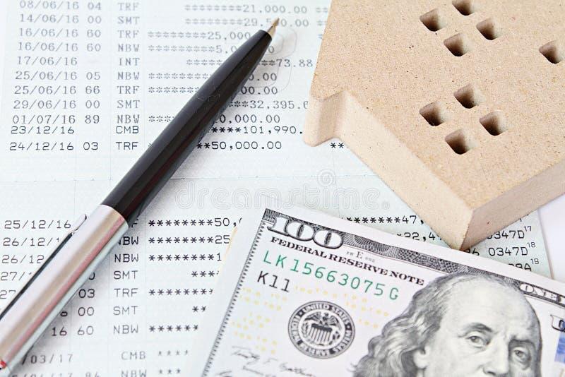 Inhysa modellen, kontanta pengar för amerikansk dollar, anteckningsboken och det sparkontobankboken eller bokföringsunderlaget på arkivbild