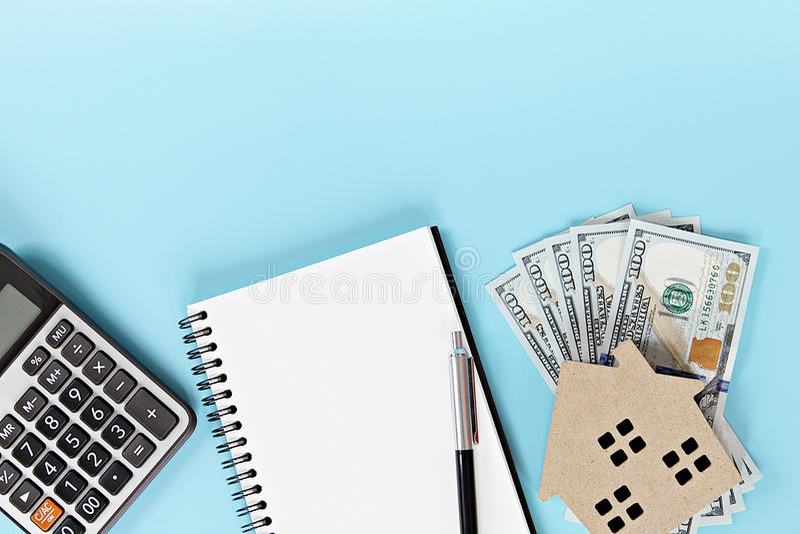 Inhysa modellen, kontanta pengar för amerikansk dollar, anteckningsboken och räknemaskinen på tabellen för kontorsskrivbordet fotografering för bildbyråer