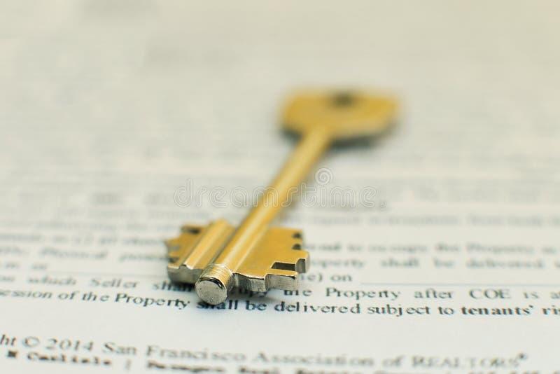Inhysa nyckel- ligga på ett avtal av försäkring för husförsäljningsarrendet eller inteckna i ett fastighetbegrepp royaltyfri bild