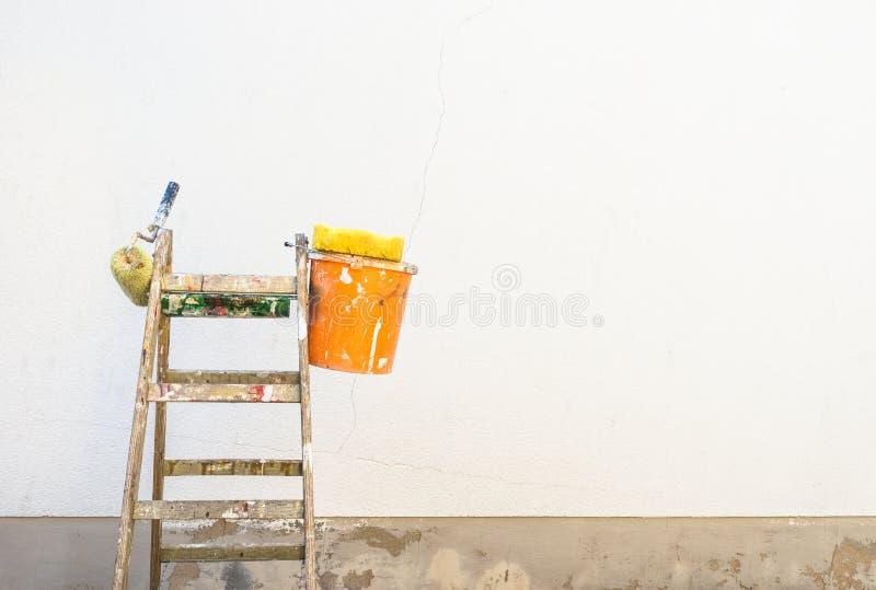 Inhysa renovering-, stege- och målaretillbehör framme av en vägg royaltyfri fotografi