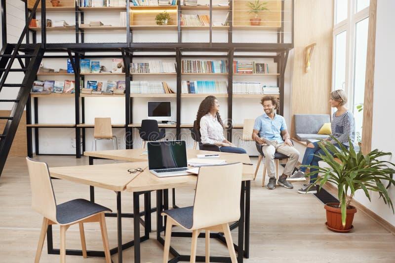 Inicio, negocio, concepto del trabajo en equipo Grupo de gente joven de la perspectiva en la reunión en la biblioteca moderna gra foto de archivo libre de regalías