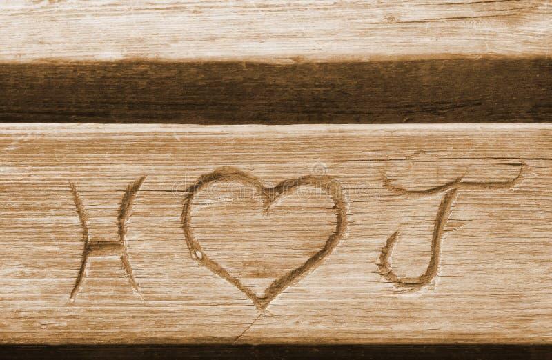 Inicjały miłość dobierają się, rzeźbią w ławki desce zdjęcia stock