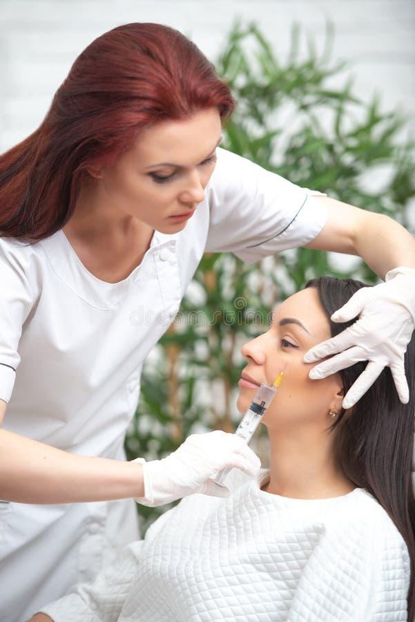 Iniezione del riempitore per il fronte Ambulatorio facciale estetico di plastica La donna di medico che fa le iniezioni con la si immagini stock