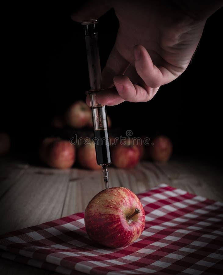 Iniezione della tossina in una mela organica immagini stock libere da diritti