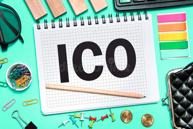 Initial coin offering. ICO with office tools on blue background. Concept of the choice ICO. A Notebook with Business notes initial coin offering ICO with office royalty free stock photos