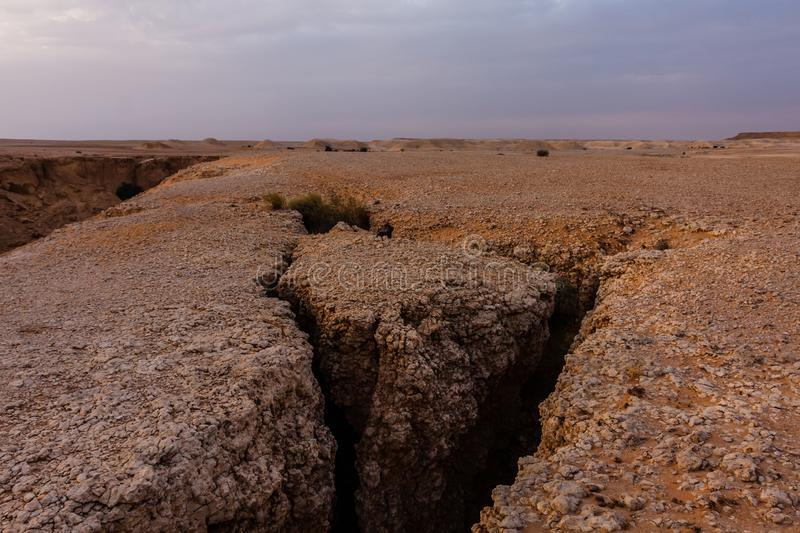 A crack at the edge of an eroded canyon on the desert south-east of Riyadh, Saudi Arabia. The initial phase of the eroding process that results in formation of a stock photos