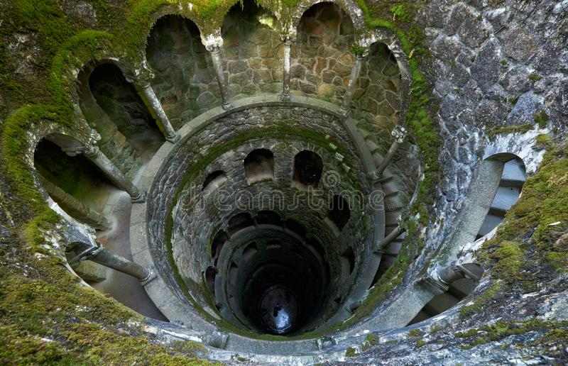 The Initiation Wells (Inverted tower) in Quinta da Regaleira estate. Sintra. Portugal. The view inside Initiation Well, whose mossy wells resemble underground stock images