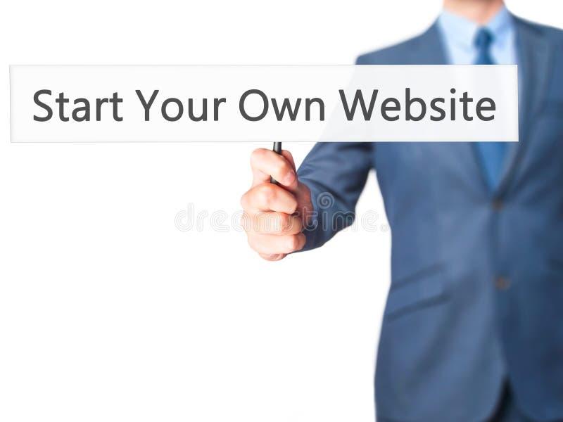 Inizi il vostro proprio sito Web - uomo di affari che mostra il segno fotografia stock