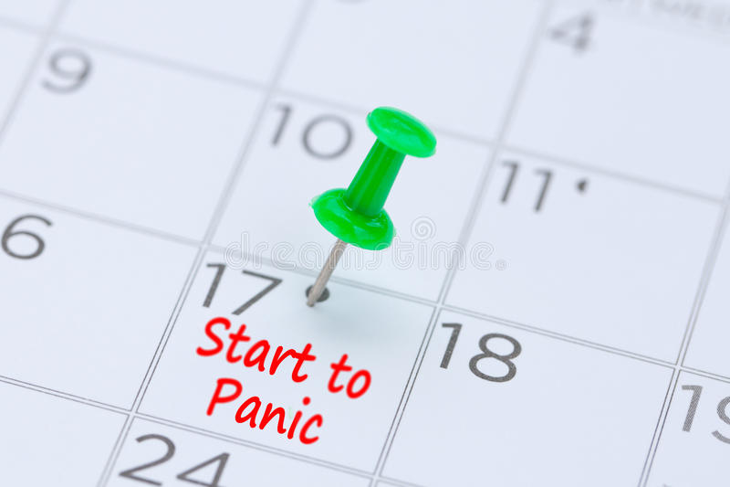 Inizi a panico scritto su un calendario con un perno verde di spinta alla r immagine stock libera da diritti
