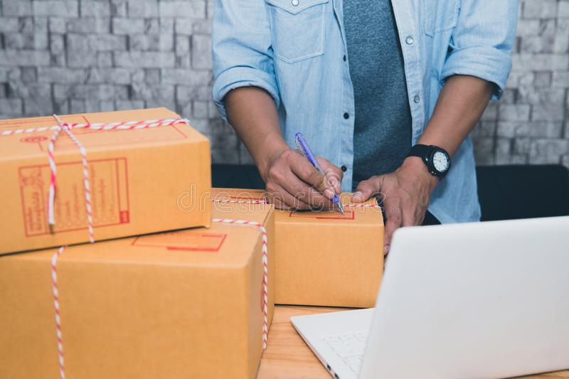 Inizi sulla PMI dell'imprenditore di piccola impresa o l'uomo asiatico indipendente che lavora con il concetto della scatola a ca fotografie stock