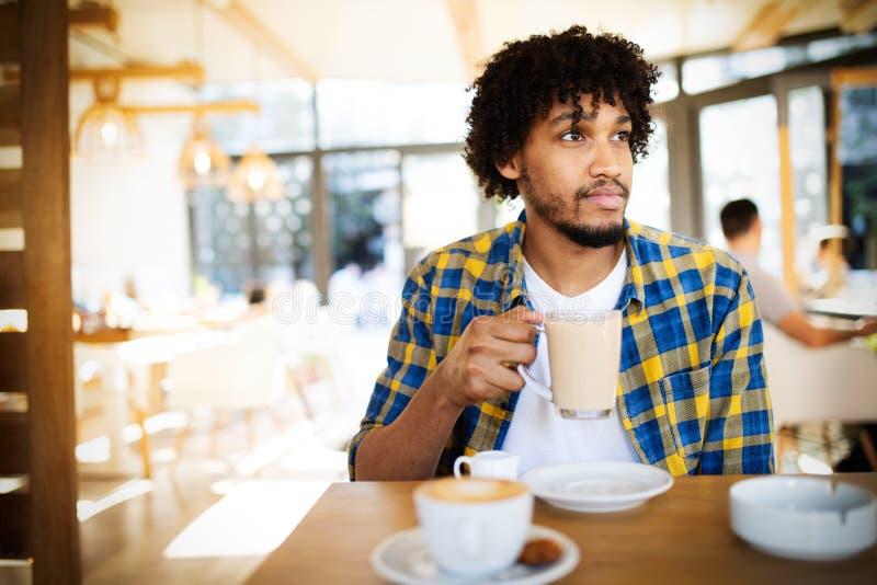 Iniziando nuovo giorno in caffè Vista laterale di giovane uomo africano che tiene la tazza di caffè a fotografia stock libera da diritti