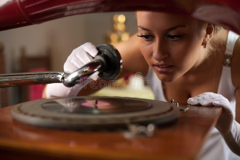 Inizio della giovane donna che gioca musica sul grammofono immagine stock