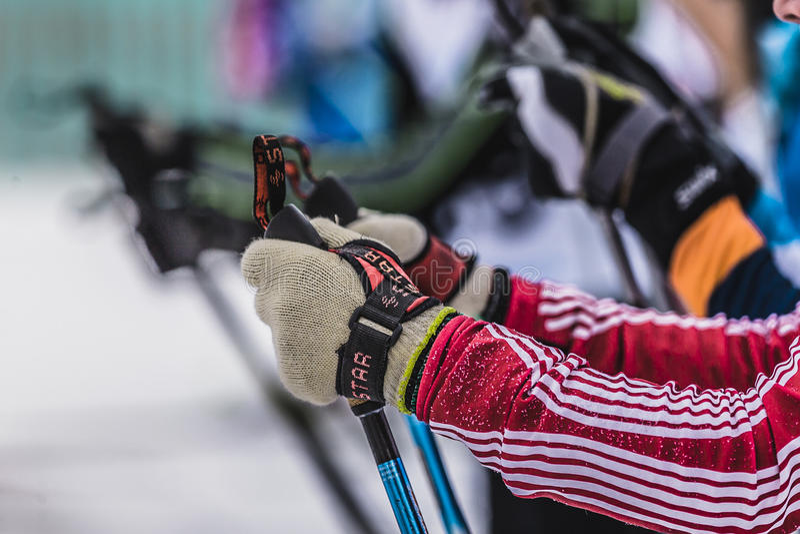 Inizio di massa degli atleti degli sciatori, del primo piano delle mani e dei pali di sci immagini stock libere da diritti