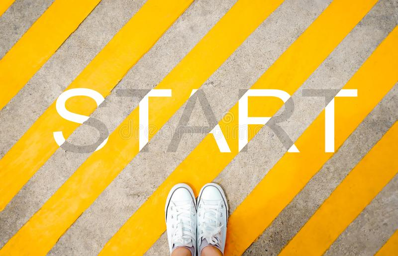 Inizio di parola e del piede scritto un fondo della strada asfaltata Piedi e gambe veduti da sopra Scarpe da tennis bianche della immagini stock libere da diritti