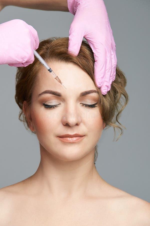 Injeção da agulha da cara Procedimento da cosmetologia da jovem mulher Luvas do doutor foto de stock royalty free