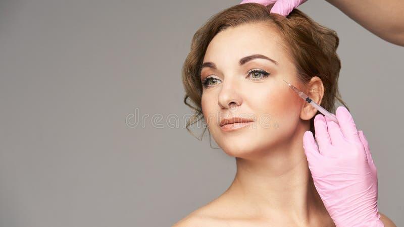 Injeção da agulha da cara Procedimento da cosmetologia da jovem mulher Luvas do doutor enrugamentos imagem de stock royalty free