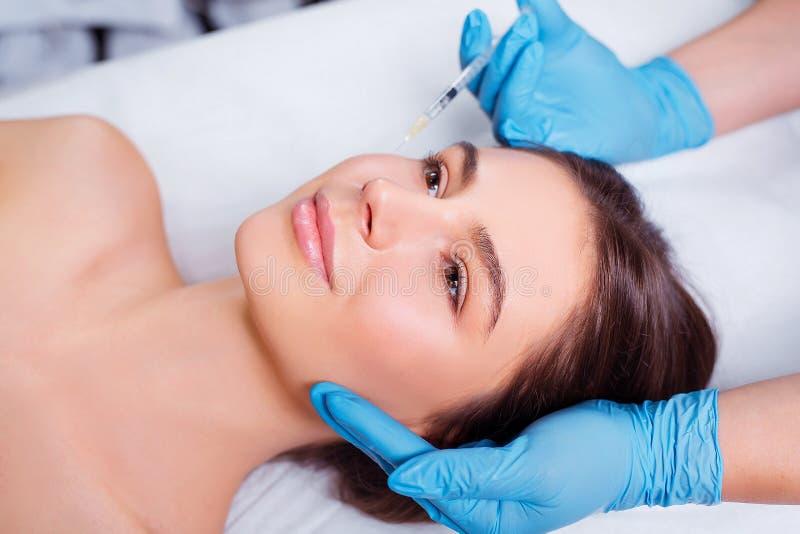 Injeção da beleza Close up do doutor Hands With Syringe perto da cara fêmea Retrato da mulher bonita que recebe o Facial imagem de stock