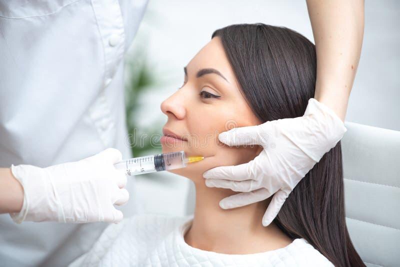 Injeção do enchimento para a cara Cirurgia facial est?tica pl?stica A mulher do doutor que dá injeções com seringa injeta os bord imagens de stock