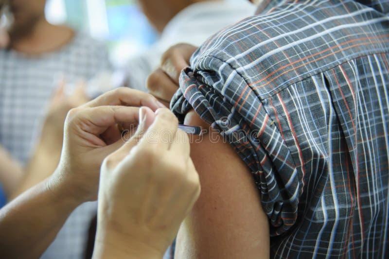 A injeção vacinal da imunização, doutor injeta a vacina ao braço paciente foto de stock