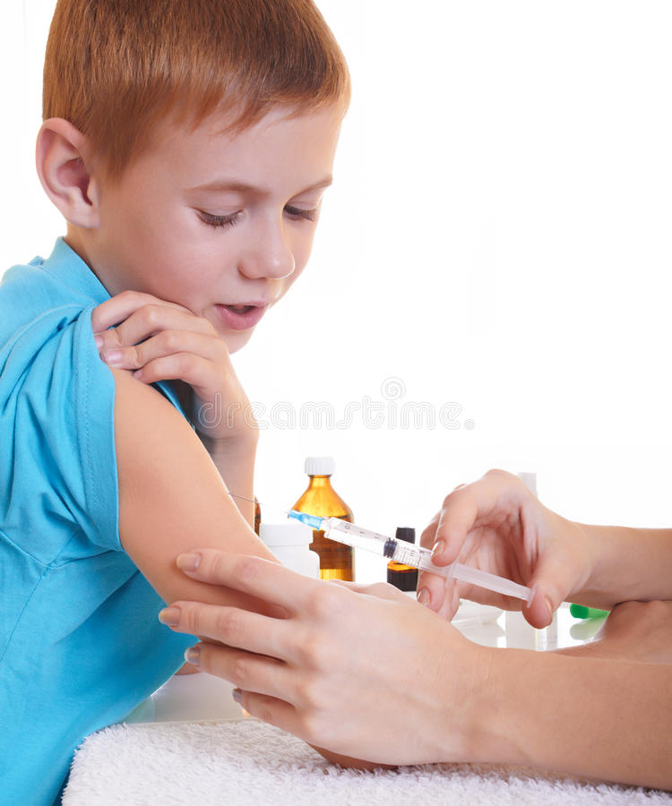 The injection. A doctor giving a child an injection royalty free stock photo