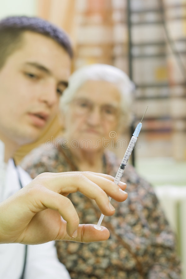 Injection. The doctor gives old woman's an injection stock photo