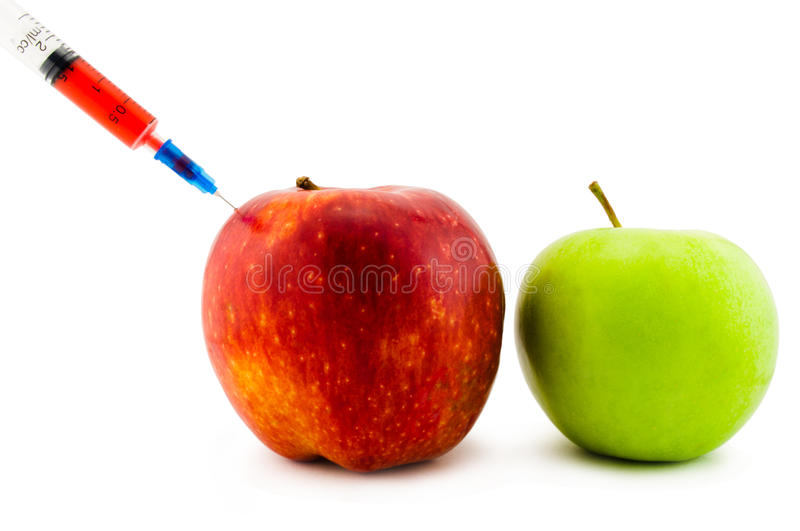 Injection in an apple. Injection of vitamins or poison in an apple stock images