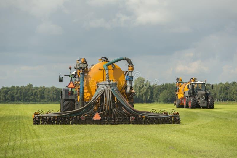 Injection de l'engrais liquide avec deux tracteurs images libres de droits