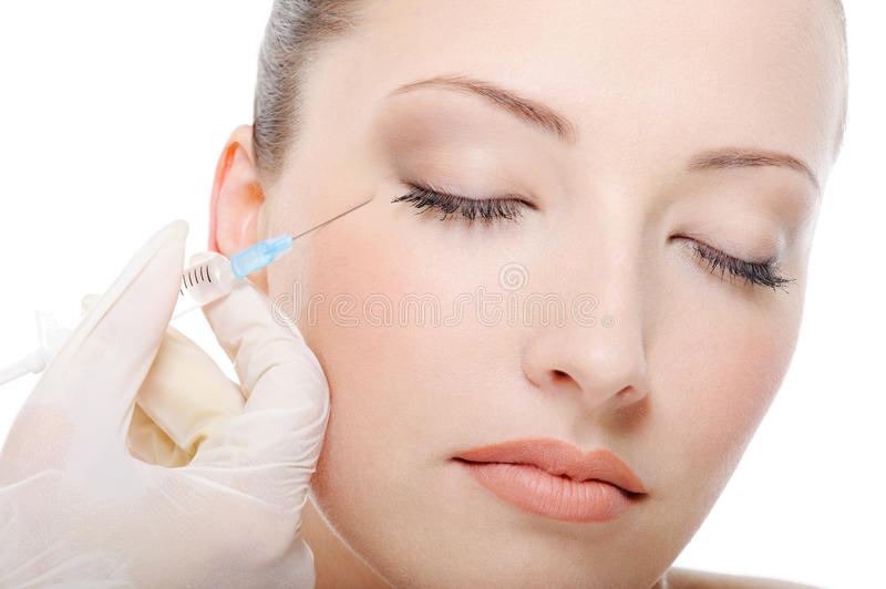 Injection in the eye. Botox injection for the beautiful young woman stock photography
