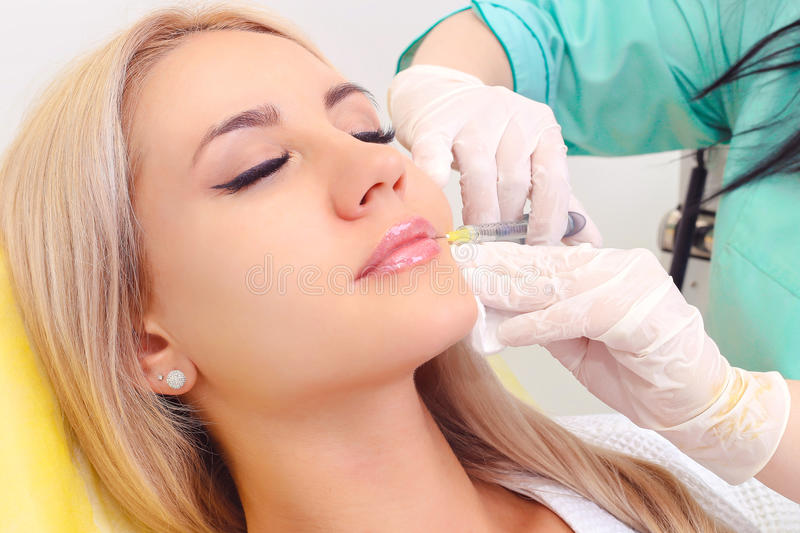 Injection in her lips and face. Beautiful girl on rejuvenation procedure in beauty clinic filler injection. Injection in her lips and face stock photography